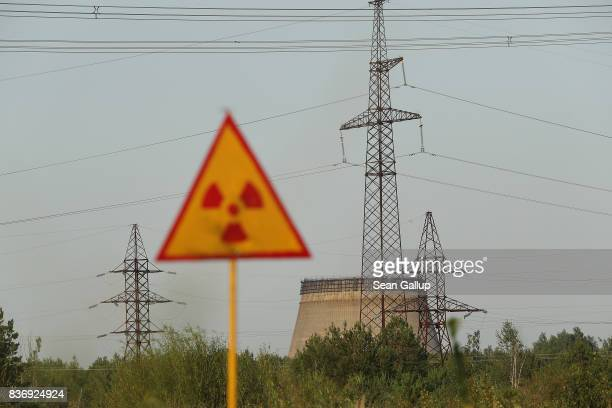 CHORNOBYL' UKRAINE AUGUST 19 A radiation sign stands near electricity pylons and a partiallyconstructed and abandoned cooling tower inside the...