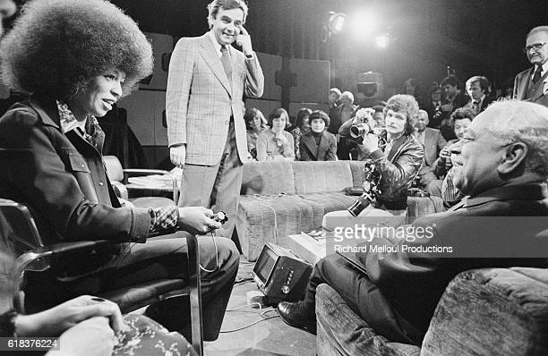 Radical political activist Angela Davis speaks with French politician Gaston Monnerville on the French television program Apostrophes as the show's...