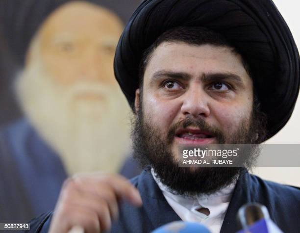Radical Shiite cleric Moqtada Sadr stands in front of a portrait of his slain father Mohammed Sadeq alSadr as he gives a press conference at the Imam...