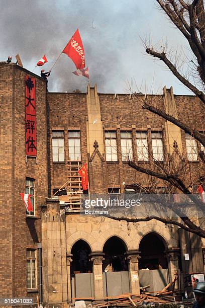 A radical student waves a flag from a tower of a building at Tokyo University January 18 as police continue an 11hour battle to regain the campus...