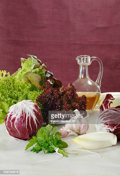 radicchio, chicory and lettuce with garlic, vinegar and bunch of herbs - cruet stock photos and pictures