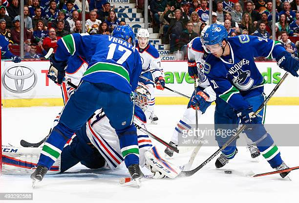 Radim Vrbata and Brandon Sutter of the Vancouver Canucks look for a loose puck in front of Anders Nilsson of the Edmonton Oilers during their NHL...