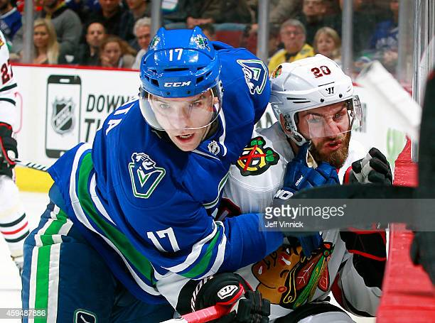 Radim Vrbata of the Vancouver Canucks rubs Brandon Saad of the Chicago Blackhawks into the boards during their NHL game at Rogers Arena November 23,...
