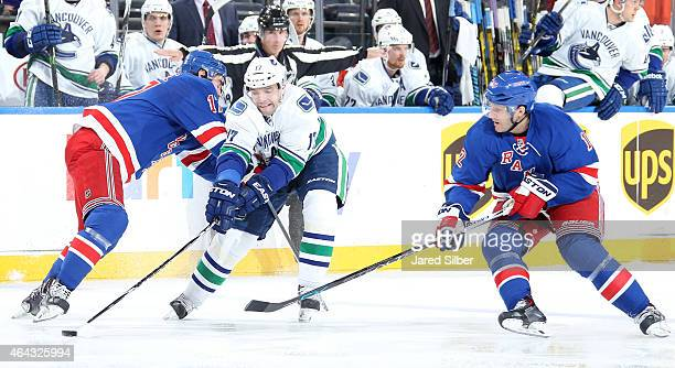Radim Vrbata of the Vancouver Canucks skates with the puck against John Moore and Lee Stempniak of the New York Rangers at Madison Square Garden on...