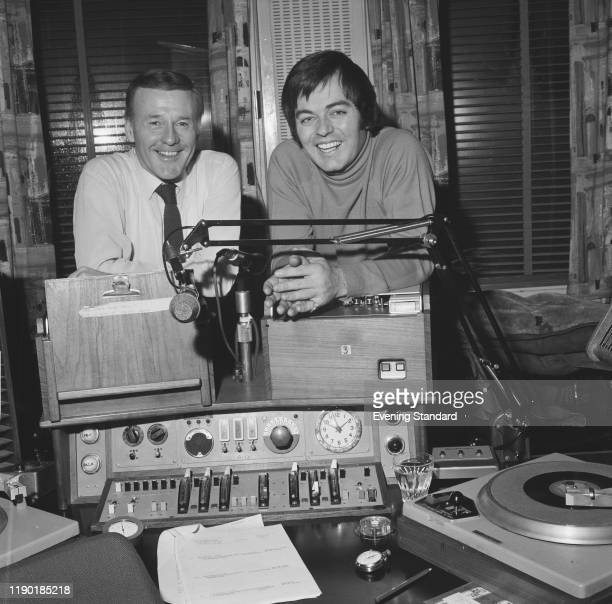 Radio 1 disc jockeys Jimmy Young , on left and Tony Blackburn stand together behind broadcast equipment in a radio studio in London on 31st December...