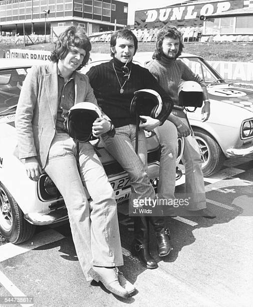 Radio 1 DJ's Steve Jones Emperor Rosko and Noel Edmonds sitting on the bonnet of a car for a racing drivers training course at Brands Hatch England...