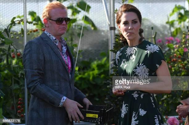 Radio 2 presenter Chris Evans watches as Catherine Duchess of Cambridge samples a tomato at the 'BBC Radio 2 Chris Evans Taste Garden' during her...