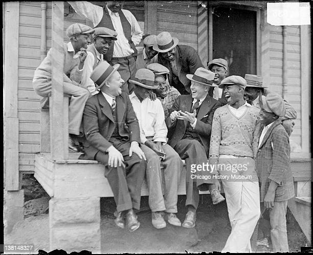 WMAQ radio actors Charles J Correll and Freeman Gosden of Amos 'n Andy sitting and laughing with a group of African American men and boys on a porch...