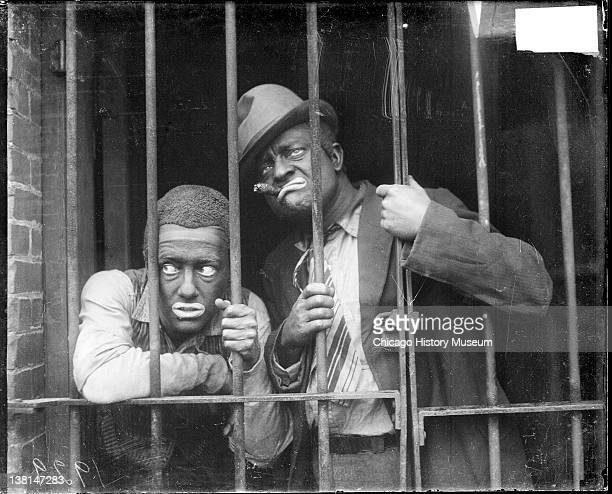 Radio actors, Charles J. Correll and Freeman Gosden of Amos 'n Andy, wearing blackface and costumes standing behind an iron gate in a building,...