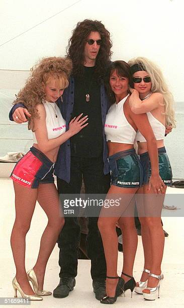 US radio anchorman Howard Stern poses with models 12 May on the beach stage of the French TV channel Canal in Cannes Stern is presenting his...