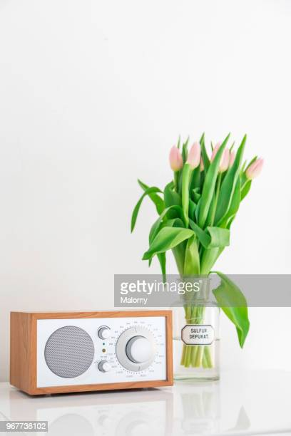 Radio and glass vase with tulips in front oh white wall. Modern interior design or modern apartment.