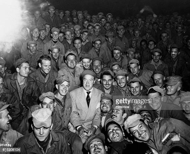 Radio and screen star Bob Hope sits with men of X Corps while members of his USO troupe entertain at Wonson Korea October 26 1950 | Location Wonson...