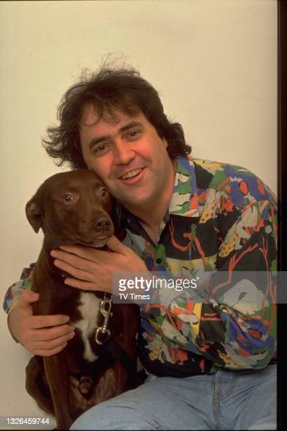 Radio and television presenter Danny Baker with a dog, circa 1990.