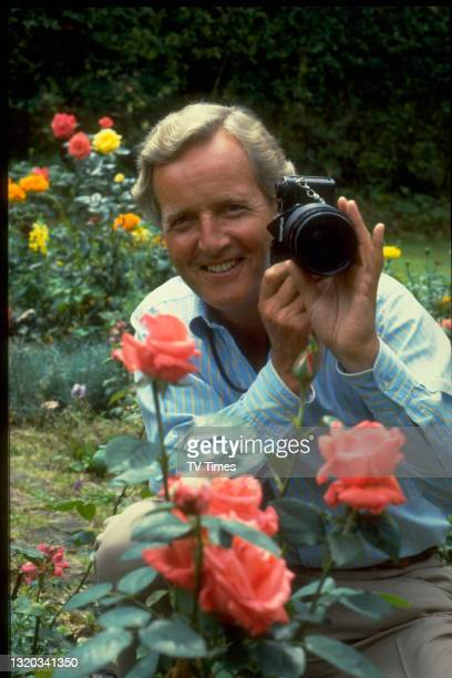 Radio and television presenter Nicholas Parsons photographing roses in a garden, circa 1983.
