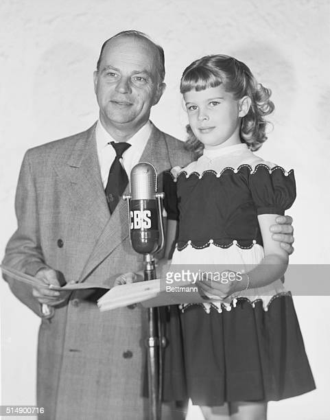 CBS radio announcer and ventriloquist Edgar Bergen and his 6yearold daughter Candice stand before a CBS microphone