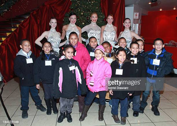 Radio City Rockettes Karen Ritchie Traci Reszetylo Taylor Shimko and Christina Cichra pose for photos with children from the Garden of Dreams...