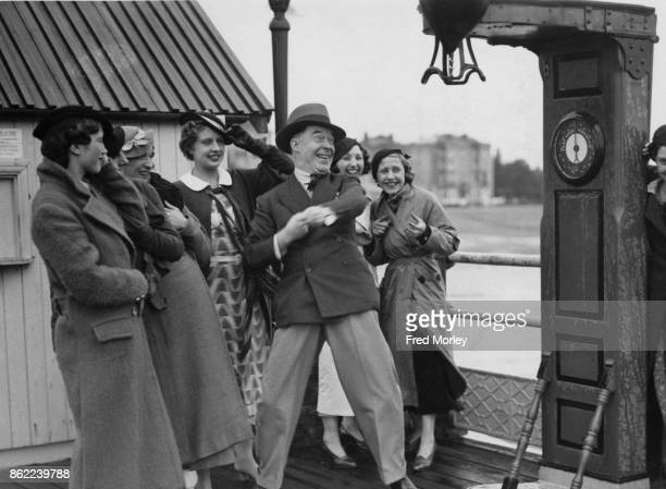 Radio comedian Leonard Henry shows off to the Eight Step Sisters on Worthing Pier UK 25th June 1934 Henry is appearing with the 'Sisters' and Beryl...