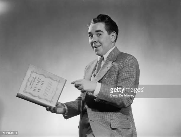 Radio comedian Ronnie Corbett posing with a book by Stanislavsky, circa 1955.