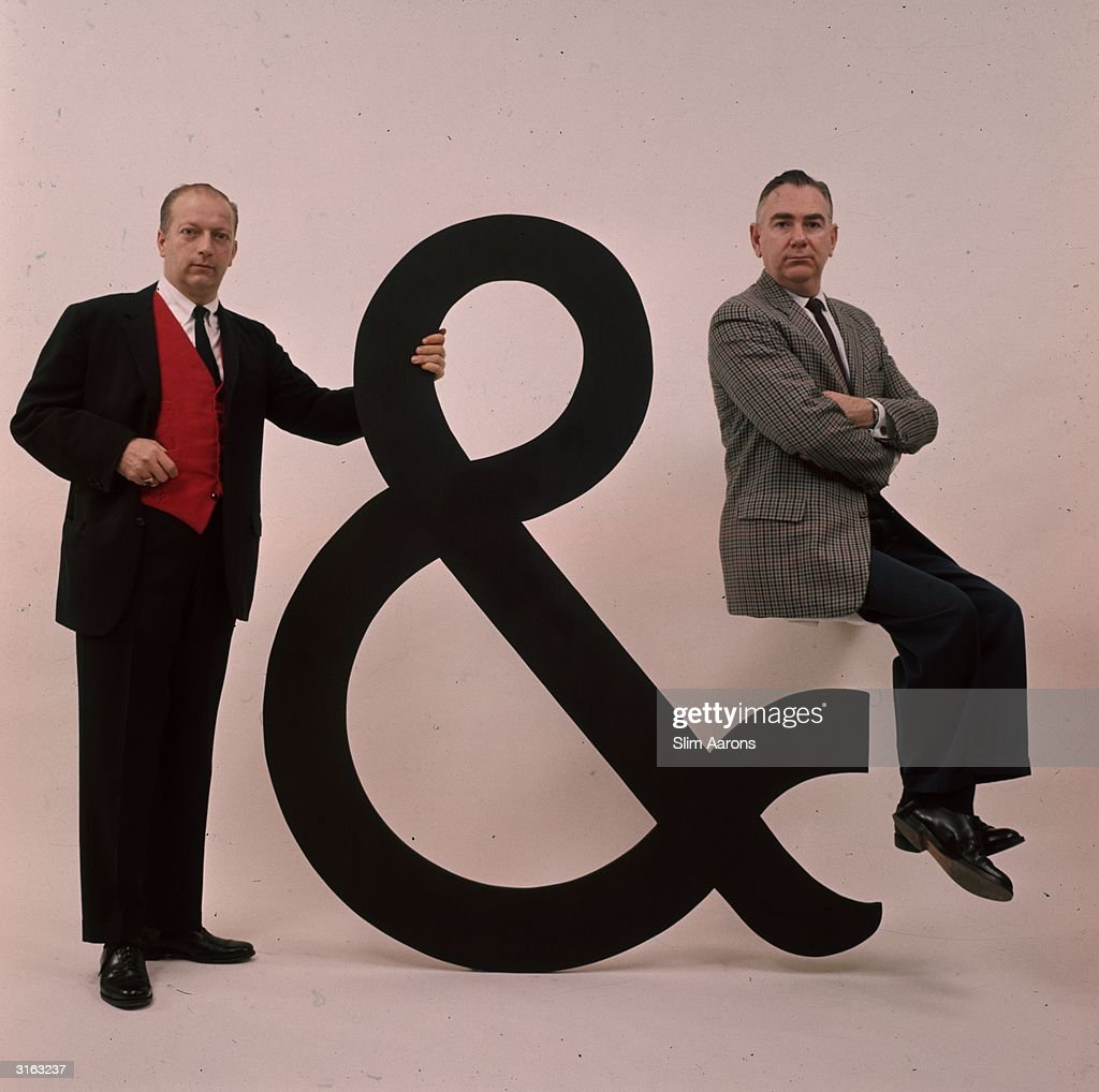 Radio comedy duo. Holding a large ampersand, Bob Elliott and on the right Ray Goulding. Exponents of dry new-England type humour in a surealsitic repertory company presentation.