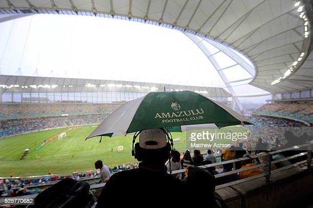 A Radio Commentator holds up an Amazulu FC umbrella in the stands during the first ever football match in the Moses Mabhida Stadium in Durban South...