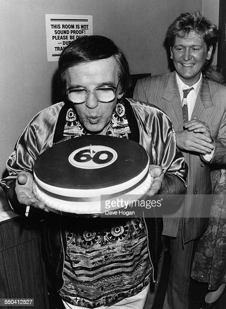 Radio disc jockey Alan Freeman blowing the candle out on top of his birthday cake celebrating his 60th birthday with fellow DJ Mike Smith circa 1987