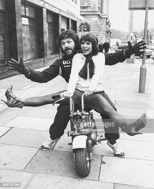 BBC Radio disc jockey Dave Lee Travis sitting on the back of a minimotorcycle with actress Judy Carne arriving at a press conference for artists...
