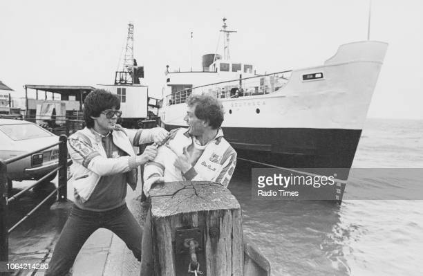 Radio disc jockeys Peter Powell and Mike Read play fighting on a dock photographed for Radio Times in connection with the BBC Radio 1 show 'Ticket to...