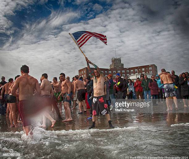 Radio DJ Gotts waves the American Flag at the Sons of Ireland Polar Bear Plunge. January 1 Asbury Park, New Jersey.