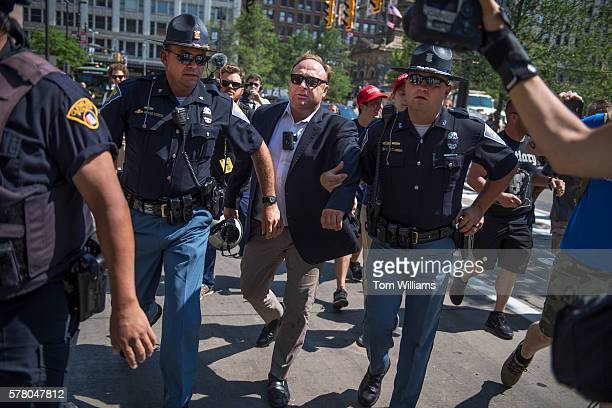 Radio host Alex Jones is escorted from a rally in the Public Square after inciting a confrontation near the Republican National Convention at the...