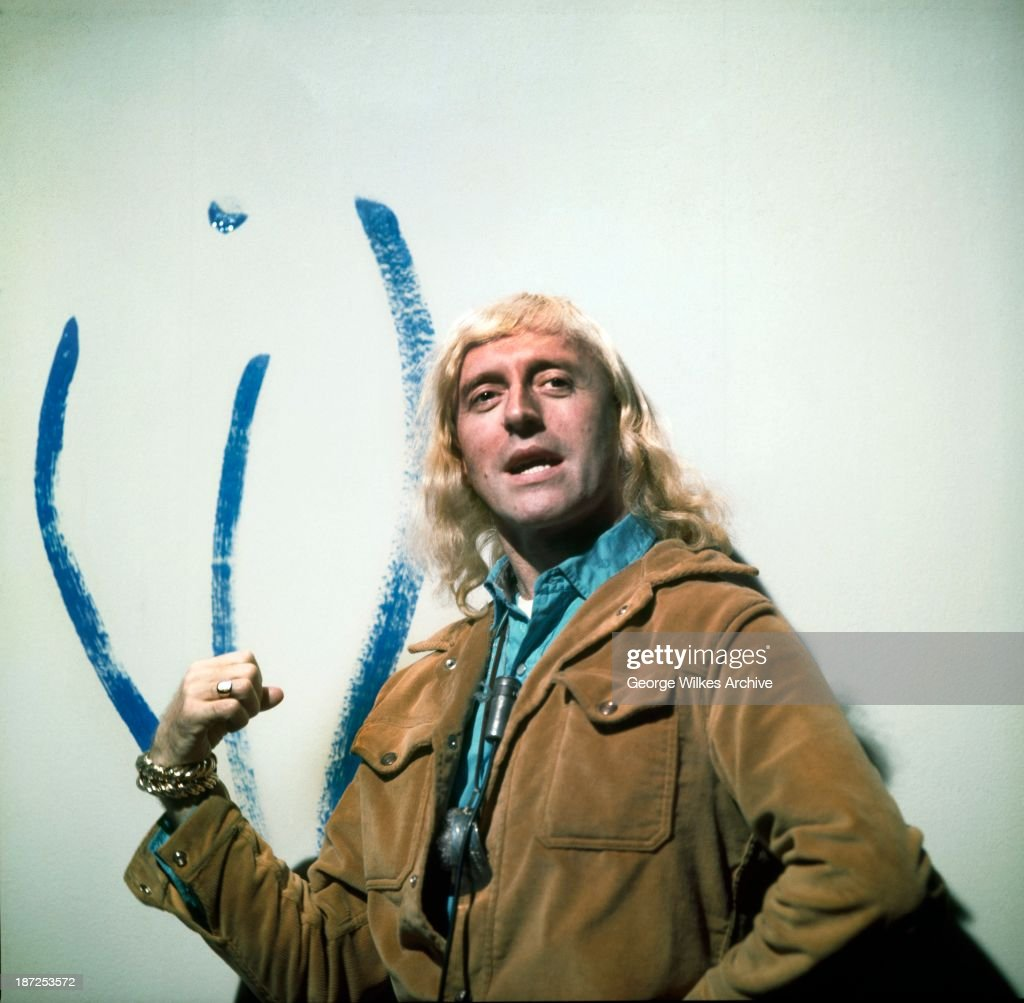Radio One disc jockey and TV presenter Jimmy Savile (1926 - 2011) photographed next to an artists impression of the female form.