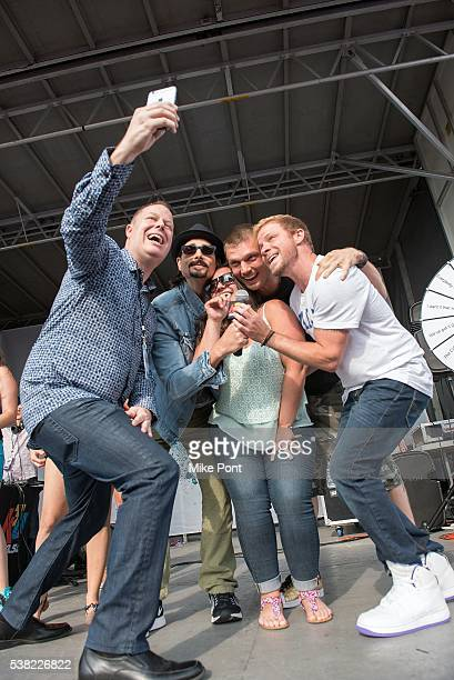 Radio personality Paul Cubby Bryant and Kevin Richardson Nick Carter and Brian Littrell of The Backstreet Boys pose for a selfie on stage during 1035...
