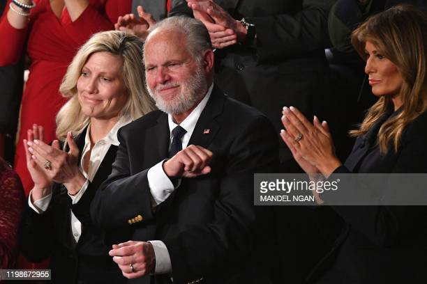 Radio personality Rush Limbaugh pumps his fist as he is acknowledged by US President Donald Trump as he delivers the State of the Union address at...