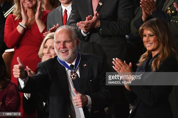 Radio personality Rush Limbaugh pumps thumb after being awarded the Medal of Freedom by First Lady Melania Trump after being acknowledged by US...