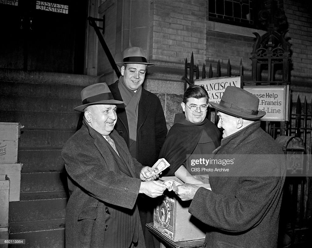 CBS Radio quiz show 'Strike It Rich' Program host, Todd Russell (standing on church steps, wearing scarf), looks on as contest winner Joseph Snyder, hands out dollar bills to men on a breadline in front of the Franciscan Monastery in New York City. Snyder, a winner of $230.00, reflected on his own breadline times. Image dated: January 19, 1948 New York, NY.