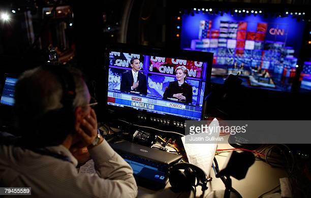 A radio reporter watches a televised broadcast of democratic presidential hopefuls US Sen Barack Obama and US Sen Hillary Clinton as they participate...