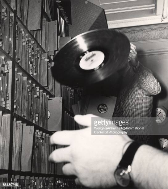 WNEW radio station disc jockey Art Ford tosses a record as an unidentified hand attempts to catch it New York 1950s Photo by Weegee/International...