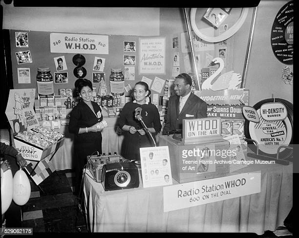 WHOD radio station disc jockey Mary Dee Hazel Garland and Walt Harper standing in WHOD booth in Syria Mosque for the 1956 Pittsburgh Courier Home...