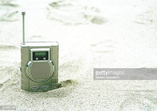 Radio sticking out of sand on beach