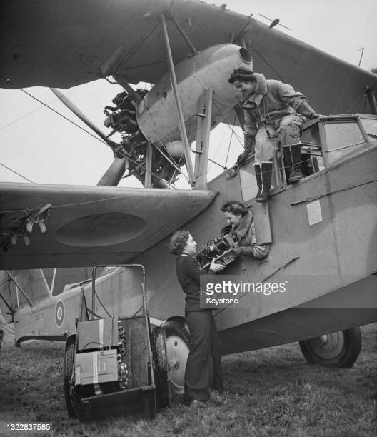Radio technician of the Women's Royal Naval Service collects a radio transmitter from the navigator as the Air Transport Auxiliary ferry pilot climbs...