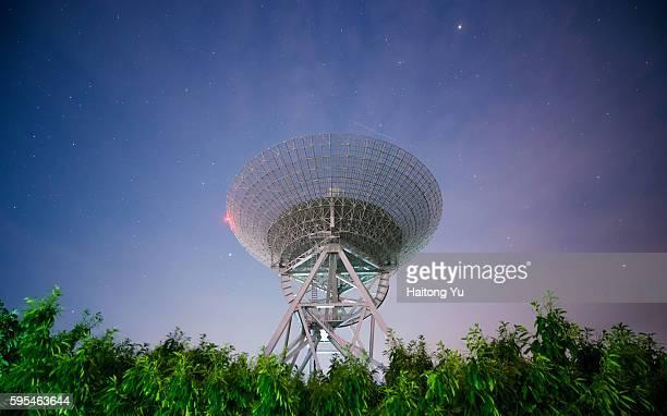 radio telescope at starry night - observatorium stock-fotos und bilder