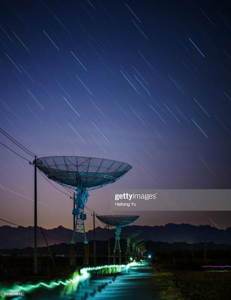 Radio telescope with star trails and light trails : Stock Photo