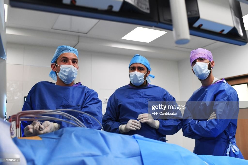 Radiologist Gilles Piana L And Assistants Stand Next To A Patient
