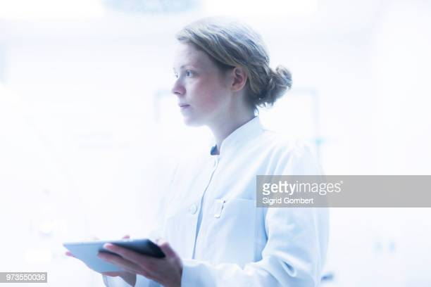 radiologist, holding digital tablet, looking away - sigrid gombert stock-fotos und bilder