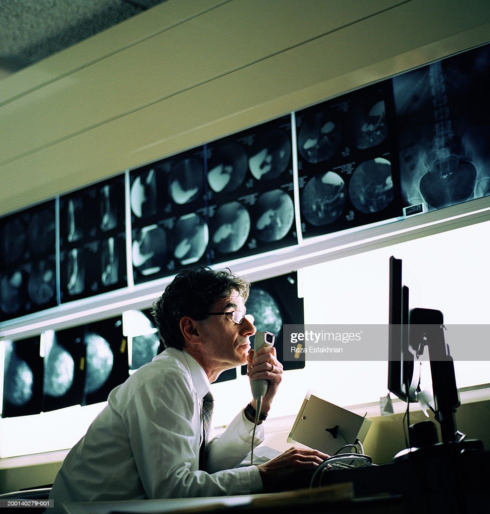 Radiologist looking at computer screen, x-rays in background : Stock Photo