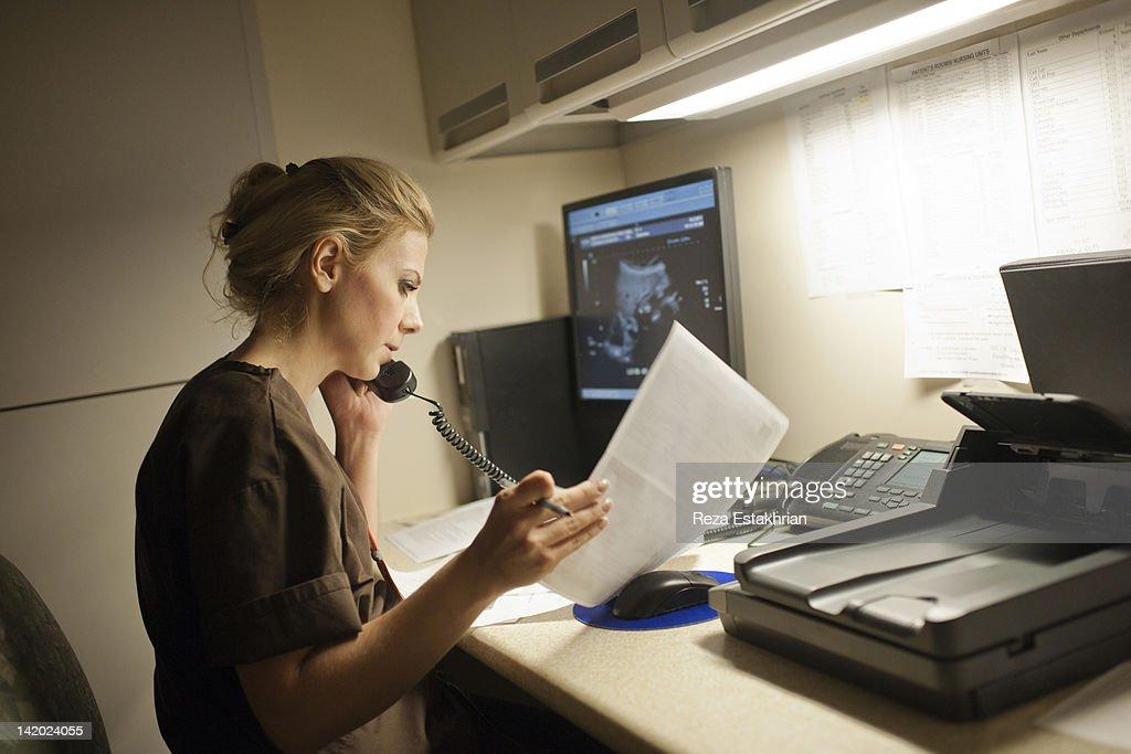 Radiologist on telephone checks notes : Stock Photo