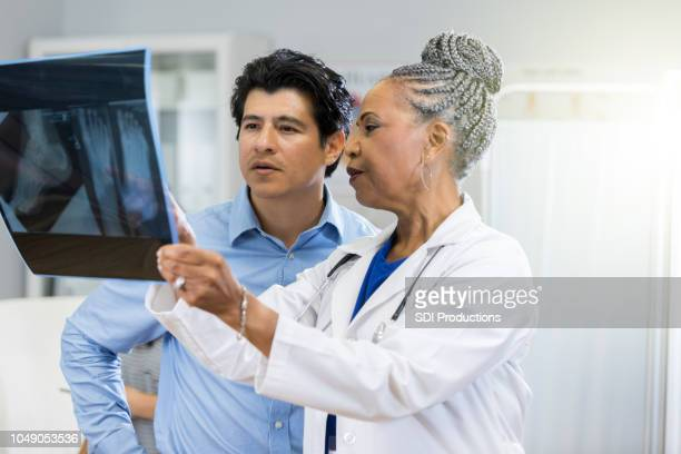 radiologist review x-ray - emergency medicine stock pictures, royalty-free photos & images