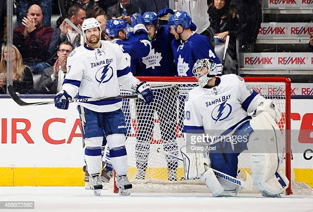 Radko Gudas and Ben Bishop of the Tampa Bay Lightning look on as Tyler Bozak James van Riemsdyk and Cody Franson of the Toronto Maple Leafs celebrate...