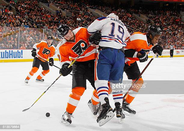 Radko Gudas and Wayne Simmonds of the Philadelphia Flyers combine on Patrick Maroon of the Edmonton Oilers during the first period at the Wells Fargo...