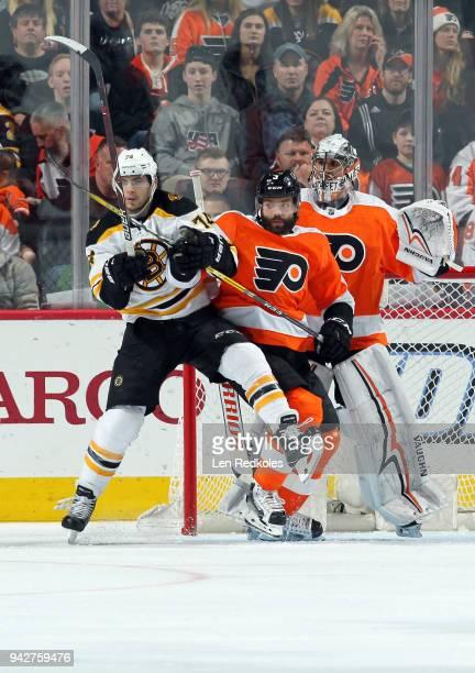 Radko Gudas of the Philadelphia Flyers battles in front of goaltender Petr Mrazek against Jake DeBrusk of the Boston Bruins on April 1 2018 at the...