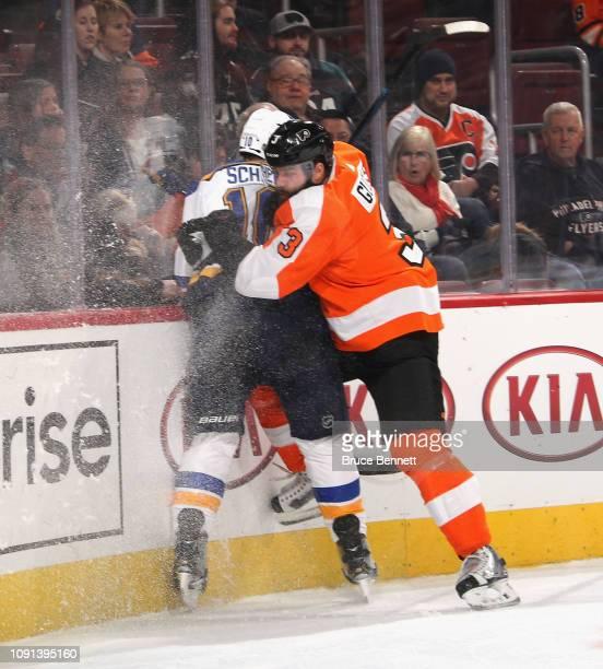 Radko Gudas of the Philadelphia Flyers checks Brayden Schenn of the St Louis Blues at the Wells Fargo Center on January 07 2019 in Philadelphia...